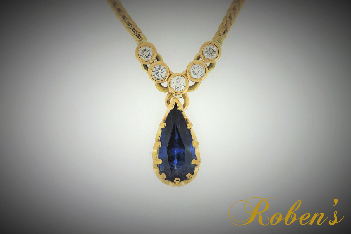 Kultainen riipus, jossa timantteja ja päärynänmuotoinen safiiri