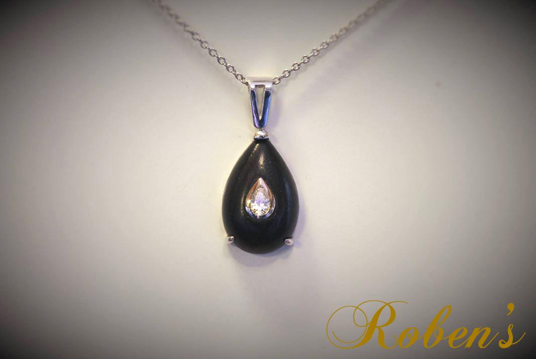 Riipus, jossa tummaa puuta ja päärynänmuotoinen timantti